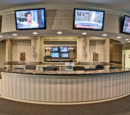 office front desk with multiple TV screens mounted on walls