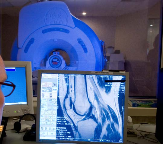 MRI machine in background with imaging monitor in foreground